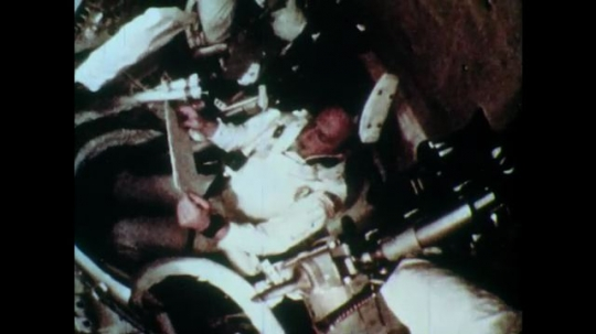 1970s man reads clipboard in cockpit of command module in zero gravity. men in headsets watch computer monitors in mission control.