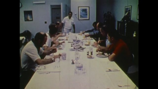 1970s: UNITED STATES: men eat breakfast. Astronauts enjoy meal before launch. Man reads newspaper