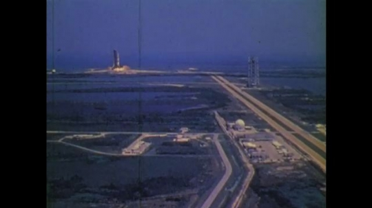 1970s: UNITED STATES: view across landscape as rocket launches from pad. Rocket in sky.