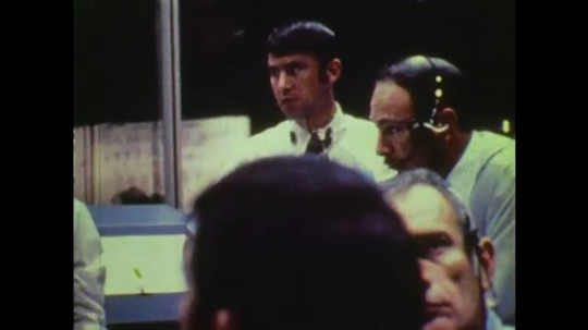 1970s: UNITED STATES: Men at mission control. Man looks at papers. Man with headset.