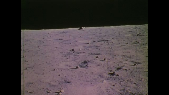 1970s: UNITED STATES: View across surface of moon from lunar module. Men at mission control watch on TV.