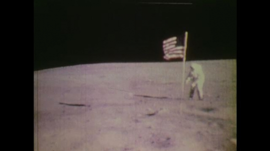 1970s: UNITED STATES: astronaut on moon next to American flag. Astronauts walk on moon. Astronaut jumps in air.