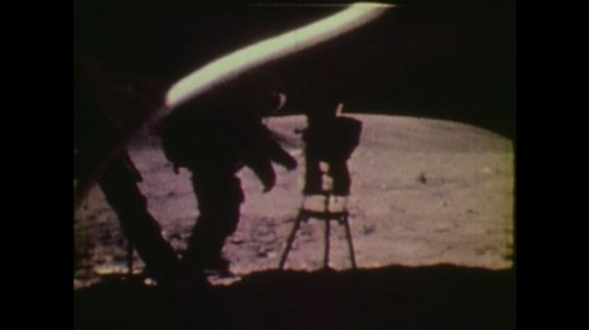 1970s: UNITED STATES: astronaut walks on moon. View of planet and galaxies from moon