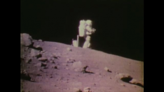 1970s: UNITED STATES: astronaut stands on surface of moon. Men at headquarters look at astronauts on television monitor