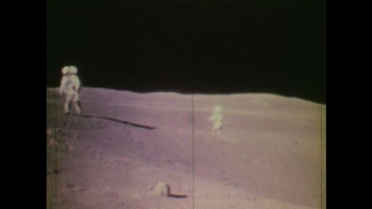 1970s: UNITED STATES: two astronauts on surface of moon. Astronaut collects samples. Mission control.