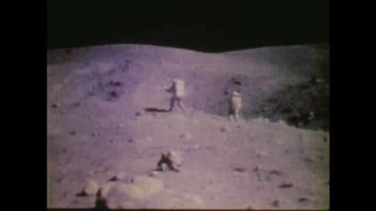 1970s: UNITED STATES: two astronauts walk across surface of moon.