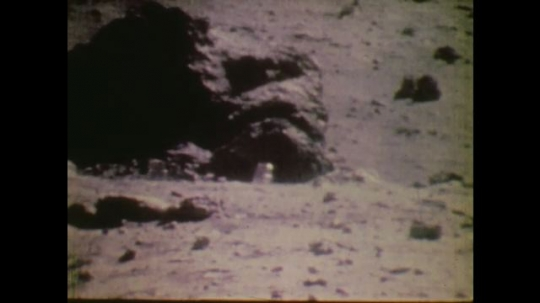 1970s: UNITED STATES: astronauts run down slope on surface of moon. Men smile at mission control