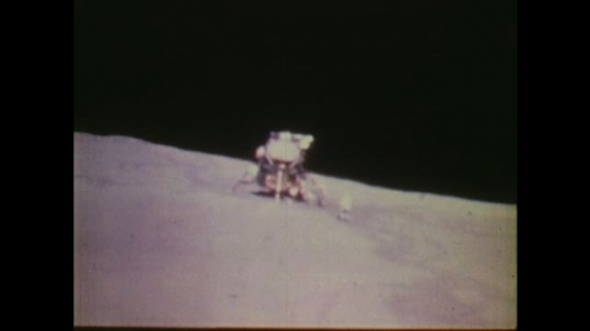 1970s: UNITED STATES: astronaut runs towards lunar module. Man at ground control