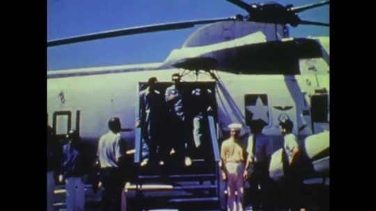 1970s: UNITED STATES: astronauts salute from helicopter on ship. Astronauts enjoy cigars. Astronauts speak to press.