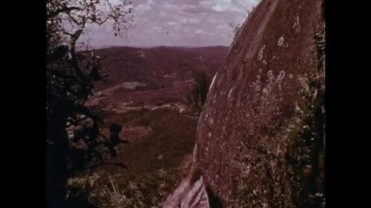 MADAGASCAR: 1970s: person wrapped in cloth and pushed over cliff. Human sacrifice. People in line.