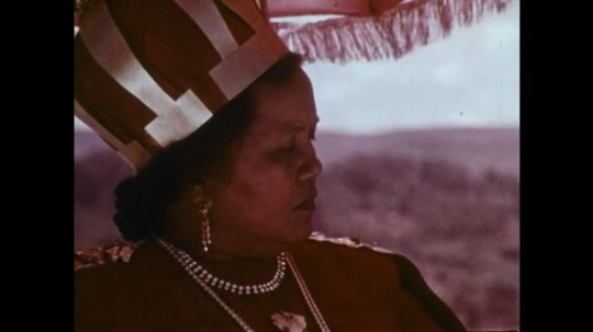 MADAGASCAR: 1970s: Queen looks across land. Hand holds letter. Girls walk through street. Men watch from street corner.