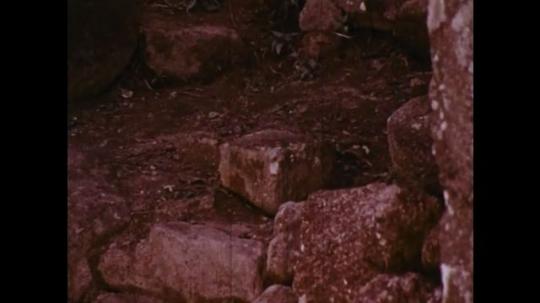 MADAGASCAR: 1970s: Rocks on ground. girl walks along path. Girl stops to pray