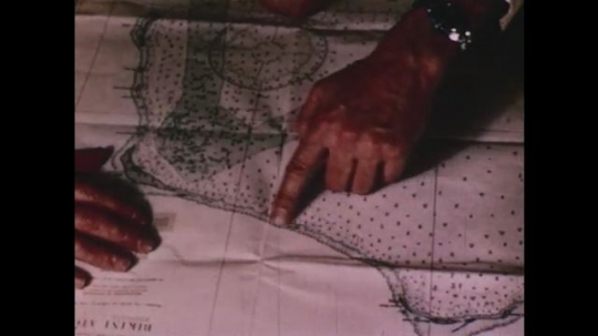 PACIFIC OCEAN: 1940s: hand points at seashore on map. Plane in sky. Plane above island runway