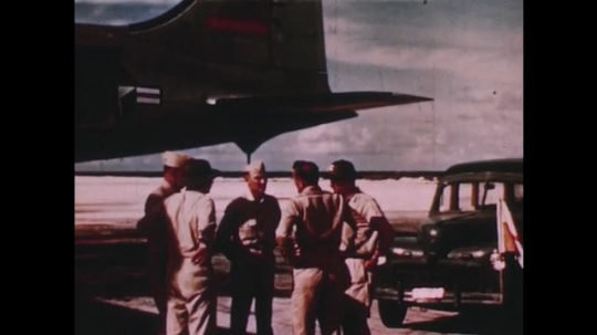 PACIFIC OCEAN: 1940s: survey members stand by plane. Man walks to car. Men on harbour side. Ship on water. Beach and coast