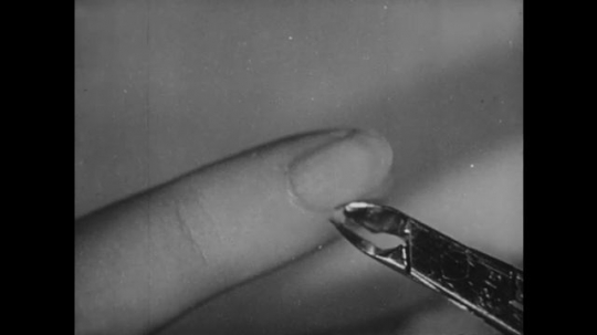 UNITED STATES: 1950s: girl cuts skin on nails. Girl trims toe nails.