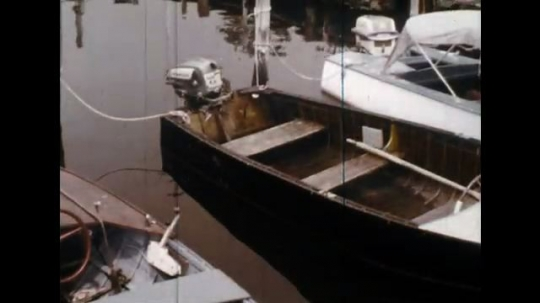 UNITED STATES: 1960s: boat moored in harbour. Boat filled with water. Wooden boat with motor