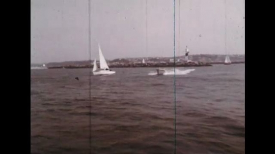 UNITED STATES: 1960s: speed boat races across water. Water leaks through boat hull. Water in boat engine.