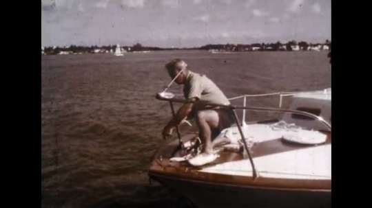 UNITED STATES: 1960s: man pulls in anchor.
