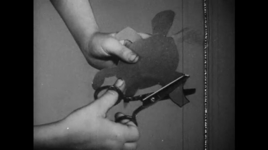 UNITED STATES: 1940s: picture of hand cutting paper. Pile of paper on floor. Cartoon mouse throws paper in bin
