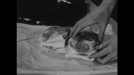 UNITED STATES: 1950s: hands take frozen burgers from pile. Frozen burgers in oven. Hands close oven door