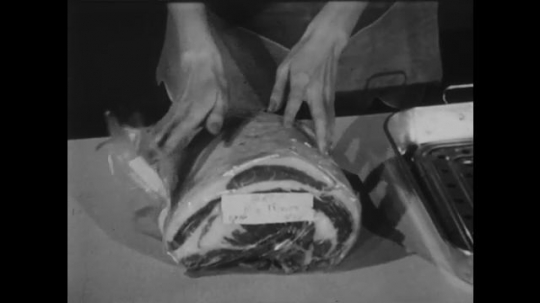 UNITED STATES: 1950s: hands unwrap meat. Lady places meat in roasting tin. Lady makes holes in meat