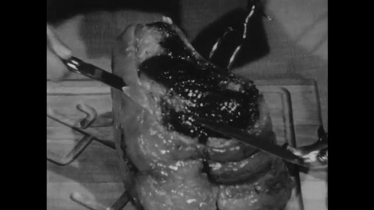 UNITED STATES: 1950s: hand carves cooked roast with knife.