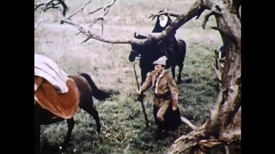 1960s: England: people on horseback along path. Nun rides horse. People arrive at house. Man sits by fire.