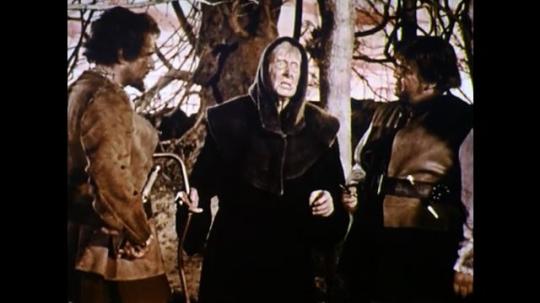 1960s: England: blind man in black cloak speaks to men