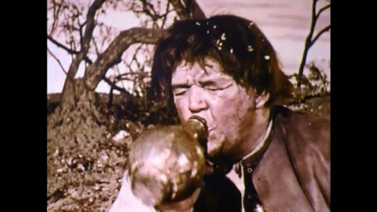 1960s: England: man drinks from pitcher. Men drink under tree. Man chokes on drink