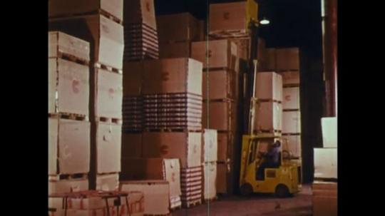 UNITED STATES: 1970s: forklift truck picks up boxes. Man drives forklift truck.
