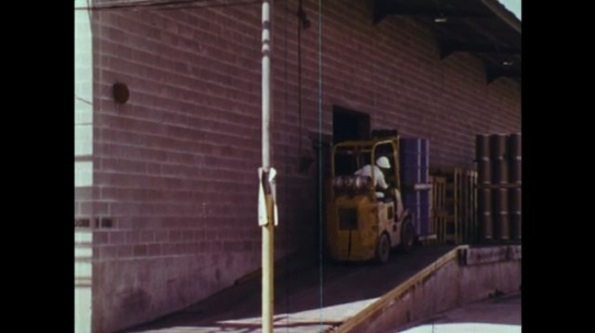 UNITED STATES: 1970s: man drives truck at work. Vehicle moves supplies