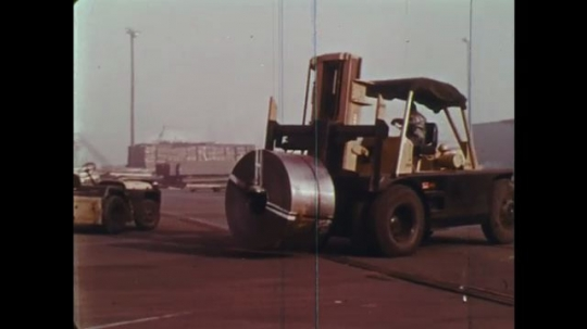 UNITED STATES: 1970s: truck moves metal. Truck moves wood. Caution sign. Explosive sign. Stop sign. Warning lights. Cars collide