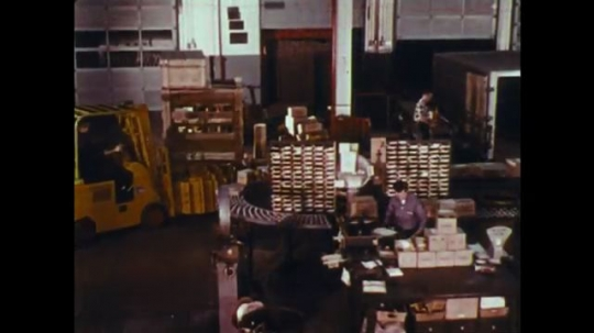 UNITED STATES: 1970s: forklift truck in workplace. Driver moves forklift truck.
