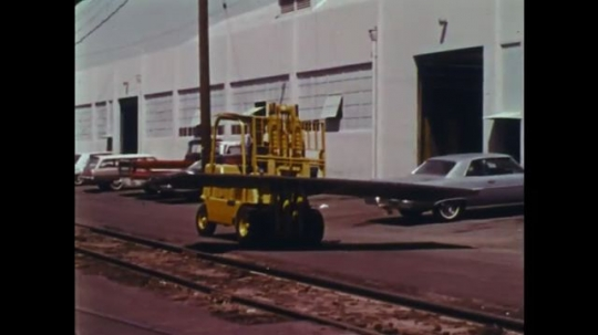 UNITED STATES: 1970s: driver lifts materials in air with forklift truck. Forklift truck falls forward.