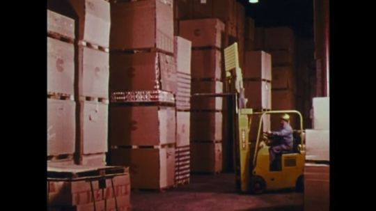 UNITED STATES: 1970s: man drives trucks towards boxes. Driver lifts high up box. Boxes fall on truck