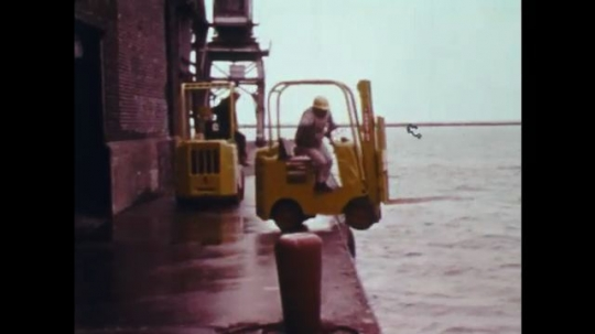 UNITED STATES: 1970s: man drives forklift truck into sea. Crane lifts truck from water