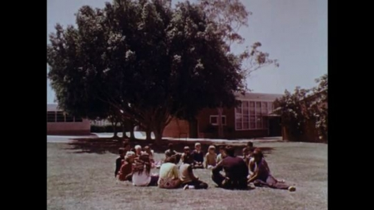 1970s: UNITED STATES: children sit outdoors at school. Girl plays with doll on floor. Shadow of man over girl. Doll on floor.