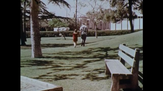 1970s: UNITED STATES: girl leaves park with man. Boy follows girl in park. Children walk past school. Man waits by car. Man talks to children outside school