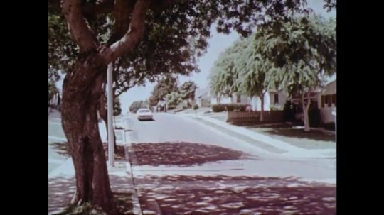 1970s: UNITED STATES: car drives down hill. Police motorbikes chase car along road. Car turns off road. Man runs from car.