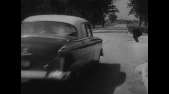 UNITED STATES: 1950s: car drives along road. Police men measure marks on road.