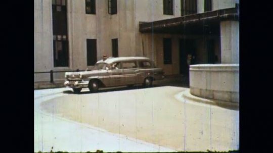 UNITED STATES: 1960s: emergency car parked by hospital. Men get into car.