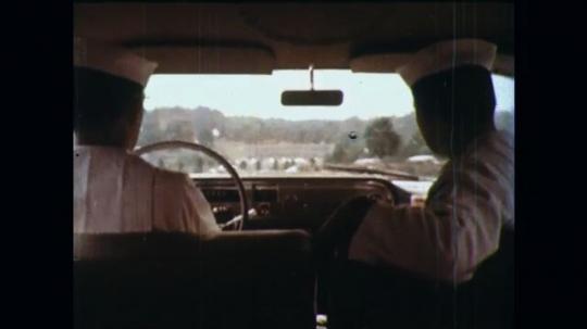 UNITED STATES: 1960s: ambulance men drive car along street. Ambulance arrives outside house. Man runs to house