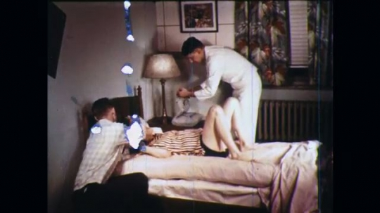 UNITED STATES: 1960s: man comforts lady during childbirth. Medic prepares instruments for childbirth.