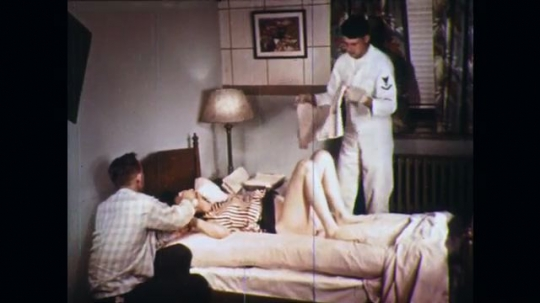 UNITED STATES: 1960s: medic places towel beneath lady