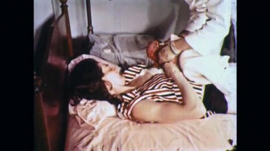 UNITED STATES: 1960s: medic gives newborn baby to mum.