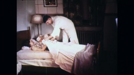 UNITED STATES: 1960s: lady lies down in bed with newborn. Medic checks on lady