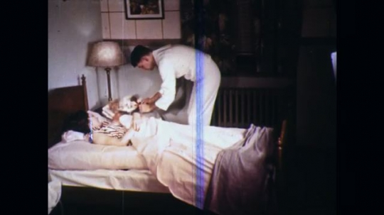 UNITED STATES: 1960s: medic examines newborn and mother at home.