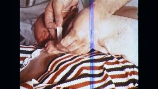 UNITED STATES: 1960s: medic attaches wrist band to newborn baby. Newborn baby breastfeeds.