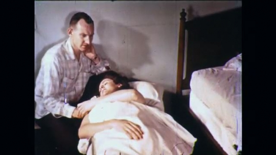 UNITED STATES: 1960s: lady lies on ambulance trolley after delivering baby