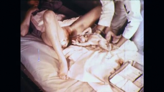 UNITED STATES: 1960s: medic places newborn baby on towel. Medic wraps baby in towel.